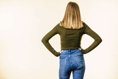 Unrecognizable woman standing backwards wearing slim fit blue jeans and khaki top, white background with copy space.