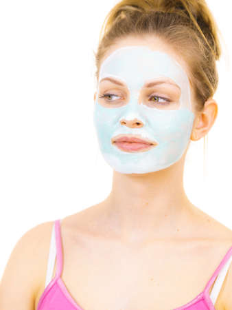Young woman with green mud mask on face, on white. Teen girl taking care of oily skin, purifying the pores. Beauty treatment. Skincare.