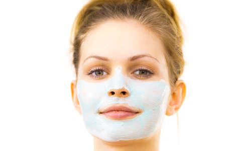 Giovane donna che applica maschera di fango verde sul viso, su fondo bianco. Ragazza teenager che si prende cura della pelle grassa, purificando i pori. Trattamento di bellezza. Cura della pelle.