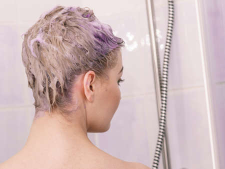 Woman having purple shampoo foam on her head under the shower. Female toning blonde hair using colored shampoo.