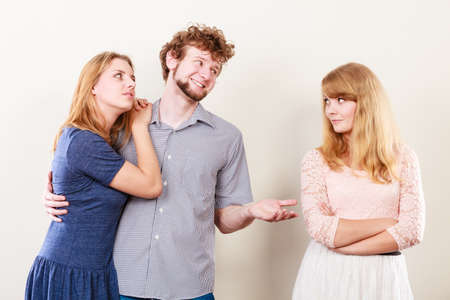 Bad relationships in triangle. Two beauty unhappy girls with sneaky cheating man.
