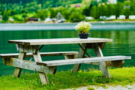 Picnic site rest stop area wooden bench and table with flowers decoration on norwegian fjord shore. Holidays relaxation on trip. Scandinavia Europe.