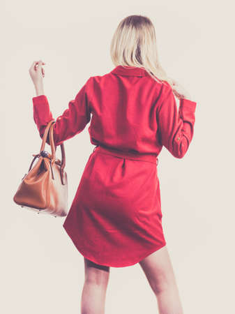 Fashionable pretty young woman wearing elegant casual red short dress and holding leather bag presenting stylish outfit. Banque d'images