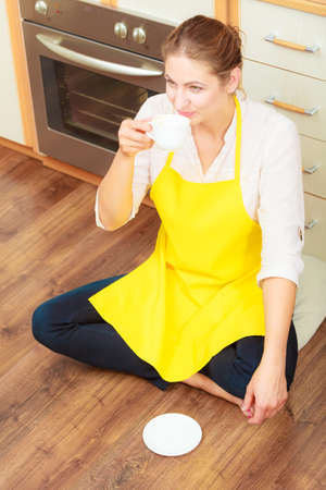 Mature woman in apron drinking cup of coffee in kitchen. Housewife female relaxing resting sitting on floor. Imagens