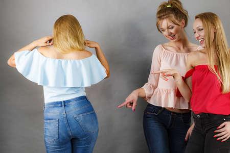 Frau, die von zwei Freundinnen gemobbt wird, die über ihre Körperform klatschen. Freundschaftsbeziehungen und Neidprobleme.