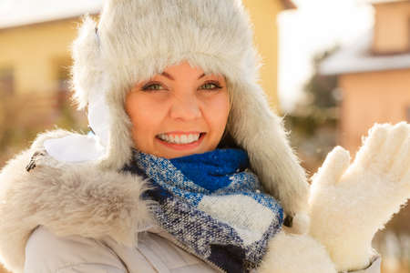 Pretty young woman wearing warm accessories during winter time. Female having grey warm hat made of light fur and blue scarf.