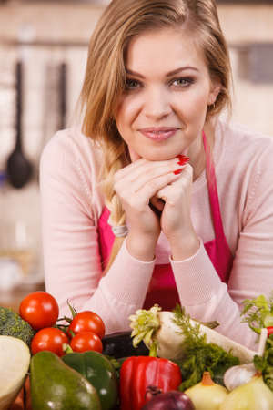 Funny joyful young woman, cooking chef having many healthy vegetables on table. Tomatoes, onion, lettuce, pepper. Vegetarian lifestyle concept.