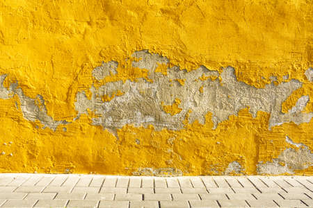 Old weathered painted yellow color peeling wall grunge background Banco de Imagens - 122683545