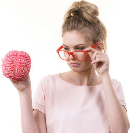 Funny blonde woman holding brain having something on mind, thinking of solution idea.