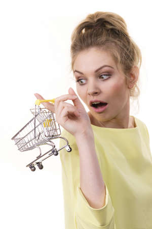 Buying things at market shops concept. Suprised woman hand holding small tiny shopping cart trolley Stockfoto