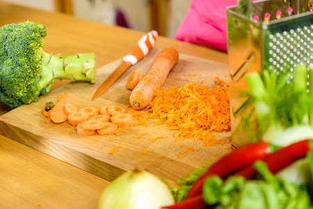 Grated orange carrot prepared for healthy meal salad. Vegetables, dieting food concept. Фото со стока
