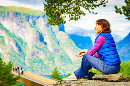 Tourist woman over Stegastein lookout looking at view of fjord mountains, Norway. Hikking, relax on trip. National tourist scenic route Aurlandsfjellet.
