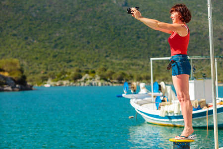 Tourism vacation and travel. Mature woman tourist in greek resort marina taking photo with camera. Sea blue background