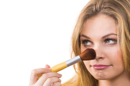 Hembra joven alegre de moda que sostiene el cepillo profesional del polvo, agregando el último toque a su maquillaje