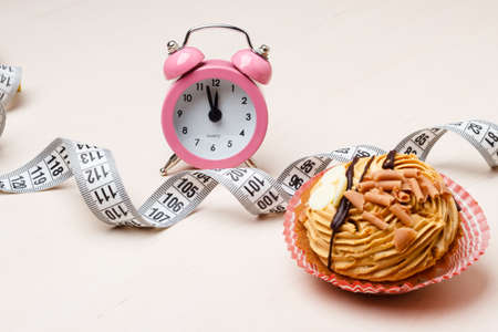 Gluttony and not eat junk sugar foods concept. Time for slimming. Cake cupcake measuring tape and alarm clock on kitchen table