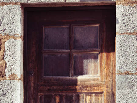 Old brown wooden made door with little window in ancient aged building made of stoens.