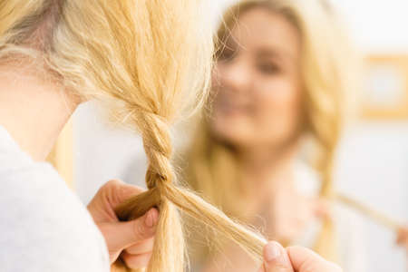 Young pretty blonde woman creating her hairstyle, making braid. Lovely female getting ready