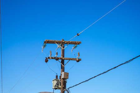 Electricity transmission pylon, power line voltage tower against blue sky.