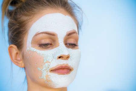 Jonge vrouw met wit gedroogd moddermasker op het gezicht dat cosmetica verwijdert. Tienermeisje dat voor een vette huid zorgt. Schoonheidsbehandeling. Huidsverzorging. Stockfoto