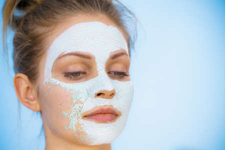 Young woman with white dried mud mask on face being removing cosmetic. Teen girl taking care of oily skin. Beauty treatment. Skincare. Imagens