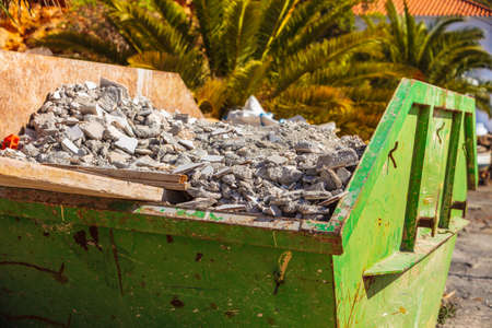 Green metal container with construction waste rubble for disposal. Heavy garbage on construction site