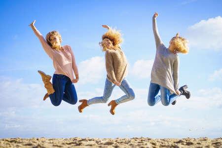Tre donne piene di gioia che saltano con il cielo sullo sfondo. Amiche che si divertono all'aperto. Archivio Fotografico