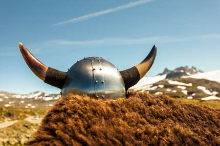 Viking helmet and brown fur on mountains nature in Norway. Tourism and traveling concept