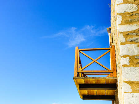 A wooden, makeshift balcony. A terrace made of wood. Details of ancient architecture against blue sky.