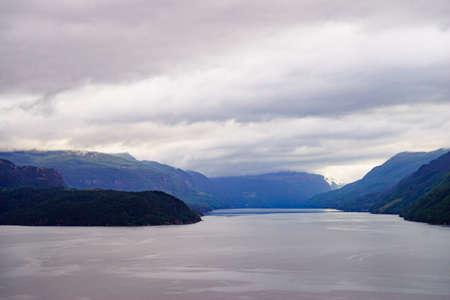 Paisaje noruego. Colinas de montañas verdes y fiordo Saudafjord en tiempo nublado. Ruta turística nacional Ryfylke.
