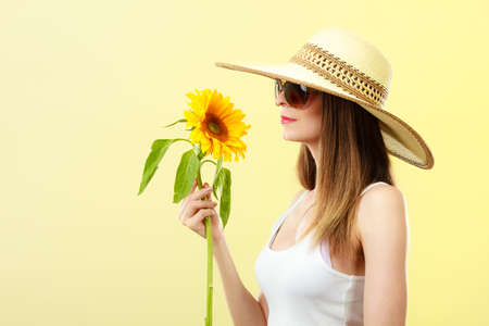 Closeup side view of attractive summer woman in sunglasses straw hat with sunflower in her hand on yellow background Stock Photo