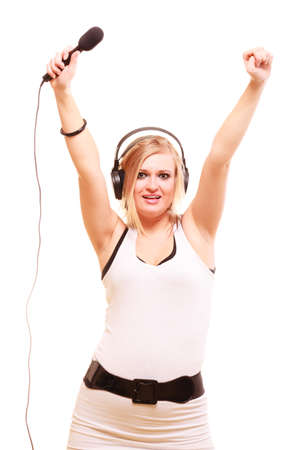 Music, passion concept. Studio shot of blonde young woman singing to microphone and wearing big headphones on her head performing songs and having fun, isolated
