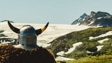 Viking warrior with helmet and fur in mountain nature, Norway. Tourism and traveling concept Stock Photo