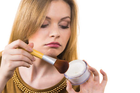 Fashionable cheerful young female holding professional powder brush, adding last touch to her make up Imagens