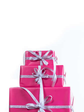 Stack of pink christmas gift box with silver ribbon on white isolated background. Xmas concept
