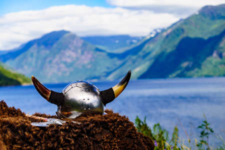 Viking helmet with axe on fjord shore in Norway. Tourism and traveling concept Stock Photo
