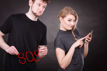 Betrayal and broken heart. Young blonde happy smiling woman flirting texting on mobile phone smartphone and sad depressed man with sos word sign symbol. Stock Photo