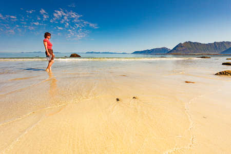 Tourist woman relaxing walking on sea shore. Coast of Gimsoya island, Gimsoysand sandy beach in summer. Nordland county, Lofoten archipelago Norway. Stock Photo
