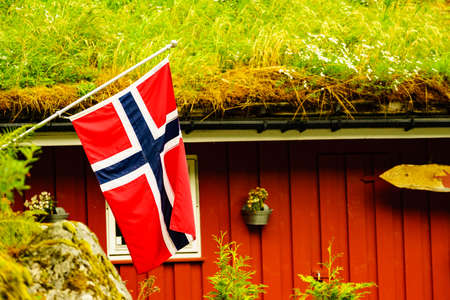 The norwegian flag waving against typical red country house with grass on the roof