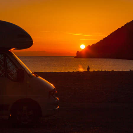 Tourism vacation and travel. Camper van on nature at sunrise over sea surface, Greece Peloponnese.