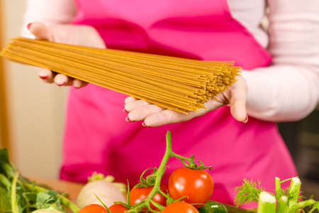 Woman holding long pasta macaroni ready to cook spaghetti. Healthy food concept.