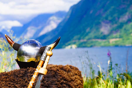 Viking helmet with weapons on fjord shore in Norway. Tourism and traveling concept Stock Photo