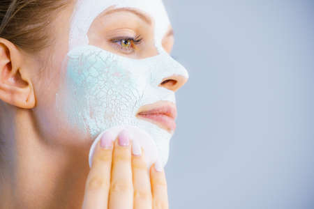 Young woman with white dried mud mask on face being removing cosmetic with cotton swab. Teen girl taking care of oily skin. Beauty treatment. Skincare. Stock Photo