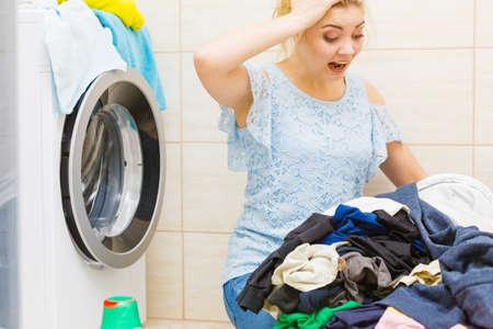 Donna infelice in bagno con mucchio di biancheria sporca e lavatrice danneggiata. Duro lavoro, lavoro domestico. Archivio Fotografico
