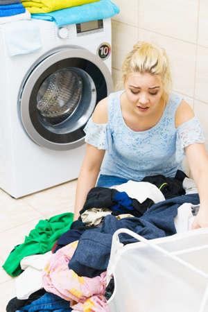 Donna triste che ha molto bucato da fare. Una donna infelice circondata da grandi pile di vestiti che si siede accanto alla lavatrice essendo stanca dei lavori domestici. Archivio Fotografico