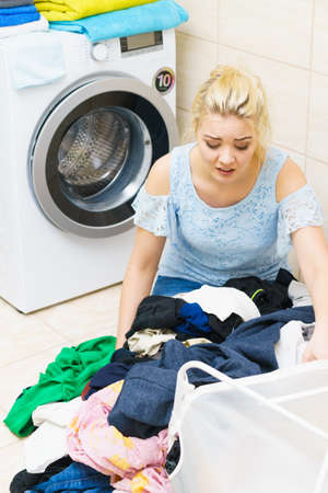 Sad woman having a lot of laundry to make. Unhappy female surrounded by big clothing piles stack sitting next to washing machine being tired houseworking. Stock Photo