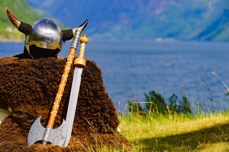 Viking helmet with weapons on fjord shore in Norway. Tourism and traveling concept