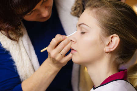 Model young pretty woman getting her eyes make up done by professional artist using brush applying eyeshadow.