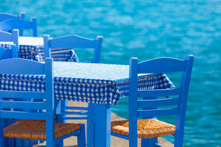 Seaside blue table and chairs open cafe outdoor restaurant in Greece on sea shore. Summer vacation on resort. Banco de Imagens