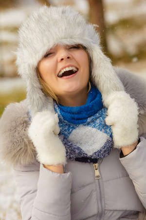 Pretty young woman wearing warm accessories during winter time. Female having grey warm hat made of light fur and blue scarf. Banco de Imagens