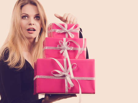 Celebration and giving concept. Blonde young woman with pink gift boxes in hands. Girl looking surprised. Banque d'images